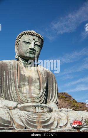 Giant Buddha of Kamakura with red apples - Stock Photo