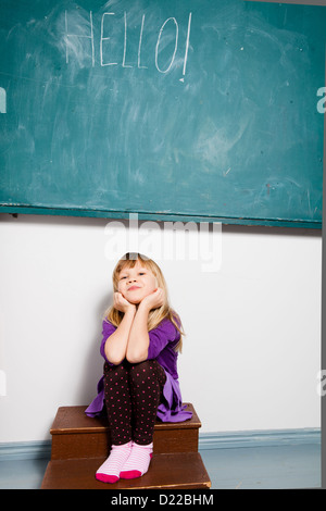 Studio portrait of smiling young girl sitting in classroom with word hello written on chalkboard - Stock Photo