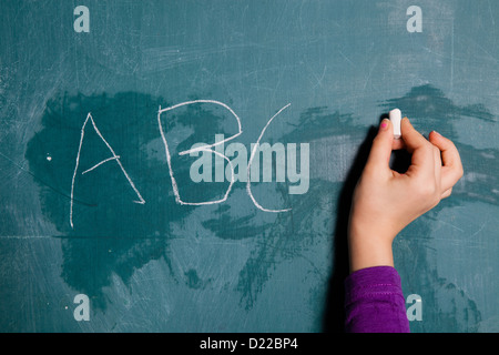 Hand of young child holding stick of white chalk to write letters of alphabet on chalkboard - Stock Photo