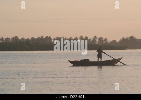 As sunrise breaks over the river, a lone fisherman steers his boat to check on his fishing nets in Hoi An Vietnam - Stock Photo