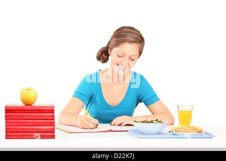 Teenage girl writing homework and having a meal isolated on white background - Stock Photo