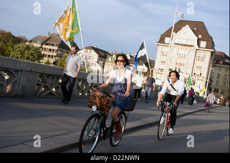 Basel, Switzerland, passersby and flags of the Basel communities on the Middle bridge - Stock Photo