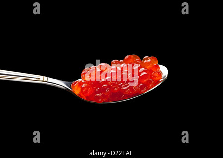 caviar red spoon against black background - Stock Photo