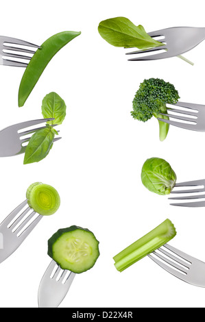 border of fresh green vegetables on forks isolated against white background. Healthy food concept - Stock Photo