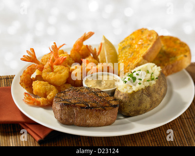 Steak and shrimp dinner served with a loaded baked potato and garlic bread - Stock Photo