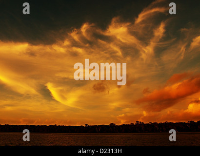 Gold Ocean Sky  - Multicolored, gold, orange,white and black turbulent wispy sunset over water and through cloud. - Stock Photo