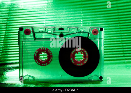 Transparent Cassette tape. Green color background. - Stock Photo