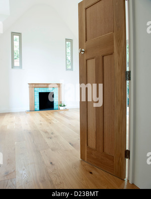 An empty room with a fireplace and wood flooring - Stock Photo
