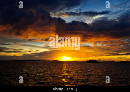 The sun setting on the flat calm ocean in Sorong Raja Ampat West Papua. Boat and Island silhouette, warm light. - Stock Photo