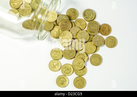 Pound coins falling from a jar - Stock Photo