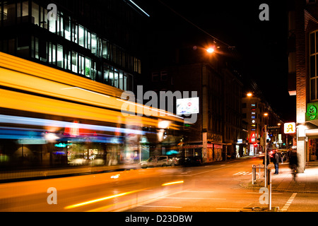Vivid night scenery showing light traces of a bus passing by in long exposure at an intersection on November 8,2012 - Stock Photo