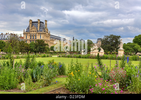 Green lawn, statues and flowers at famous Tuileries Garden and Louvre museum on background under cloudy sky in Paris, - Stock Photo