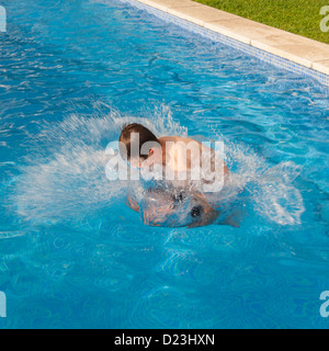 A 12 year old boy jumping in a swimming pool - Stock Photo