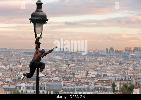 acrobatic performance artist at an old gas lamp on the hill of Sacre Coeur and view of Montmartre and Paris - Stock Photo