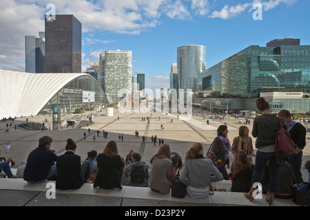 young people on stairs of La Grande Arche with view to the towers of the financial district La Défense in Paris - Stock Photo