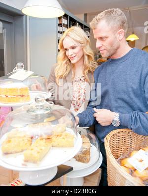 A couple choosing cakes in a delicatessen - Stock Photo