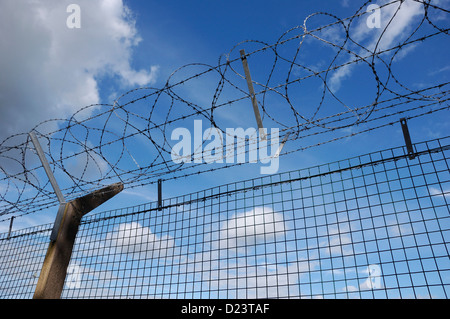 Security fencing with razor-wire against a blue and cloudy sky - Stock Photo