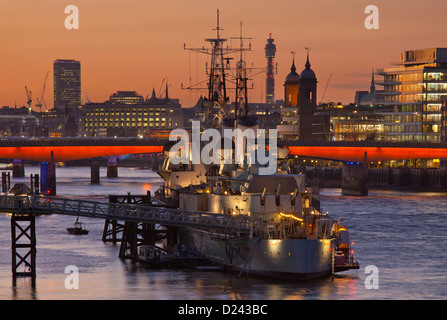 HMS Belfast moored on the Thames with London bridge skyline and post office tower in background at sunset, London, - Stock Photo
