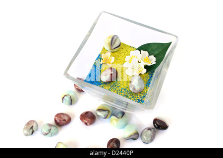 Vase with colorful sand, stones and flowers on white background. - Stock Photo