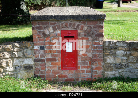 Red post box set into wall on village green - Stock Photo