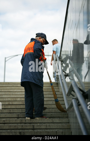Minsk, Belarus, a street cleaner sweeping staircases - Stock Photo
