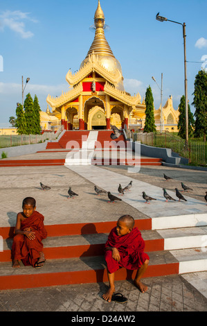 Two young novice Buddhist monks sitting on steps outside Maha Wizaya Pagoda in Yangon - Stock Photo