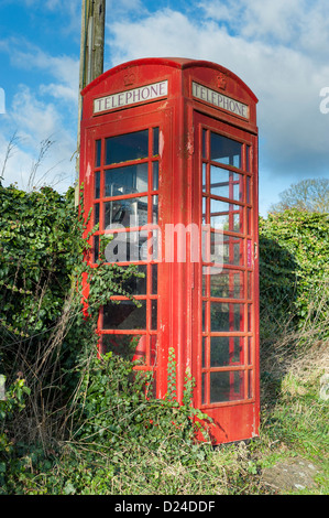 Unkempt, overgrown, red, BT Telephone Box with adjacent post box - Stock Photo