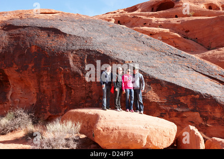 tourists posing in front of rock covered in petroglyphs along mouses tank trail valley of fire state park nevada - Stock Photo