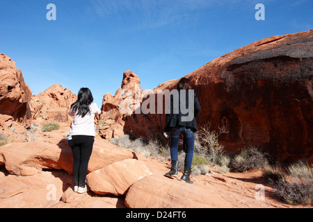 two female asian tourists walking up to rock covered in petroglyphs along mouses tank trail valley of fire state - Stock Photo