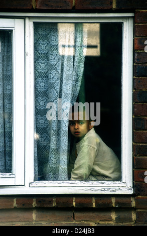 Young child looking forlornly out of window on rundown council housing estate, Lambeth, London, UK. - Stock Photo