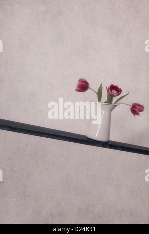three tulips in a vase on a lopesided wooden board - Stock Photo