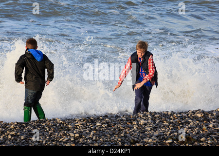 Two boys enjoy playing by the splashing waves at water's edge on Penmon beach on Isle of Anglesey, North Wales, - Stock Photo