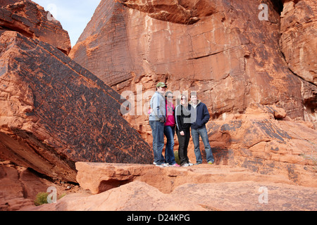 tourists pose in front of petroglyphs on atlatl large rock valley of fire state park nevada usa - Stock Photo
