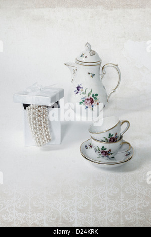 two vintage coffee cups, a coffee pot and a present box with a pearl necklace - Stock Photo