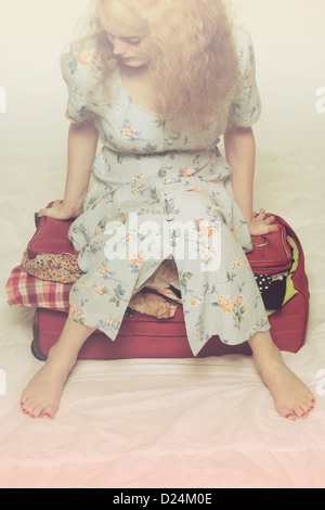 a woman tries to close a suitcase by sitting on it - Stock Photo
