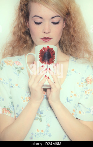 a woman in a floral dress is drinking out of a mug - Stock Photo