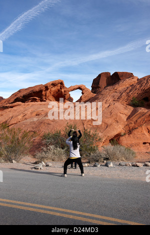 two female asian tourists pose and take photos in front of arch rock in the valley of fire state park nevada usa - Stock Photo