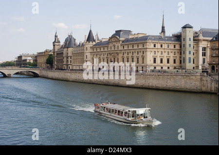 Paris, France, an excursion boat on the Seine in the light of the Conciergerie - Stock Photo
