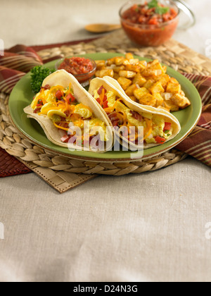 Breakfast egg tacos served with potatoes and salsa - Stock Photo