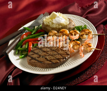 Steak and shrimp skewer dinner with loaded baked potato and vegetables - Stock Photo