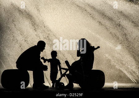 Silhouette Of A Couple With Young Boy In Front Sunlit Water Fountain