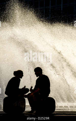 Silhouette Of A Young Couple With Ice Cream In Front Sunlit Water Fountain