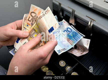 Berlin, Germany, the money in the cash register is counted - Stock Photo