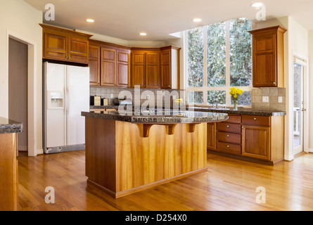 Modern daylight kitchen with solid red oak flooring, cherry wood cabinets, stone counter to and gas stove range - Stock Photo