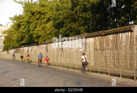 People cycling along the Berlin Wall in Niederkirchner Street. Berlin. Germany. - Stock Photo