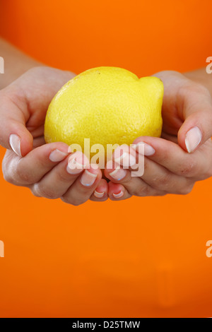 lemon in woman hands close up - Stock Photo