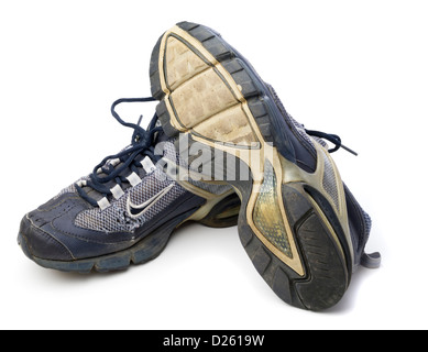 One pair of old blue Nike running shoes isolated on white background - Stock Photo