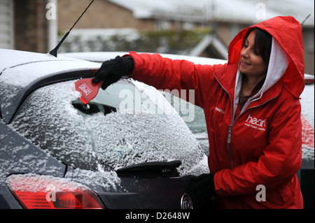 Young woman dressed in Heart FM radio station jacket clearing snow and ice from Vauxhall Corsa car using a Heart - Stock Photo