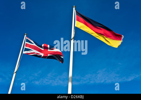 The Union Flag of the United Kingdom and the German Flag fly side by side. - Stock Photo