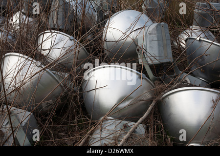 Street lamps lie abandoned in the weeds in a municipal dumping area. - Stock Photo
